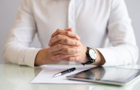 Close-up of male executive sitting at table with clasped hands. Caucasian hr manager working at table with papers and digital tablet. Employment concept